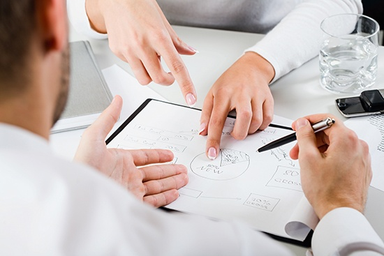 Solution driven, employees discussing a document