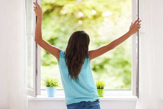 Positive impact, woman looking through a PVC window