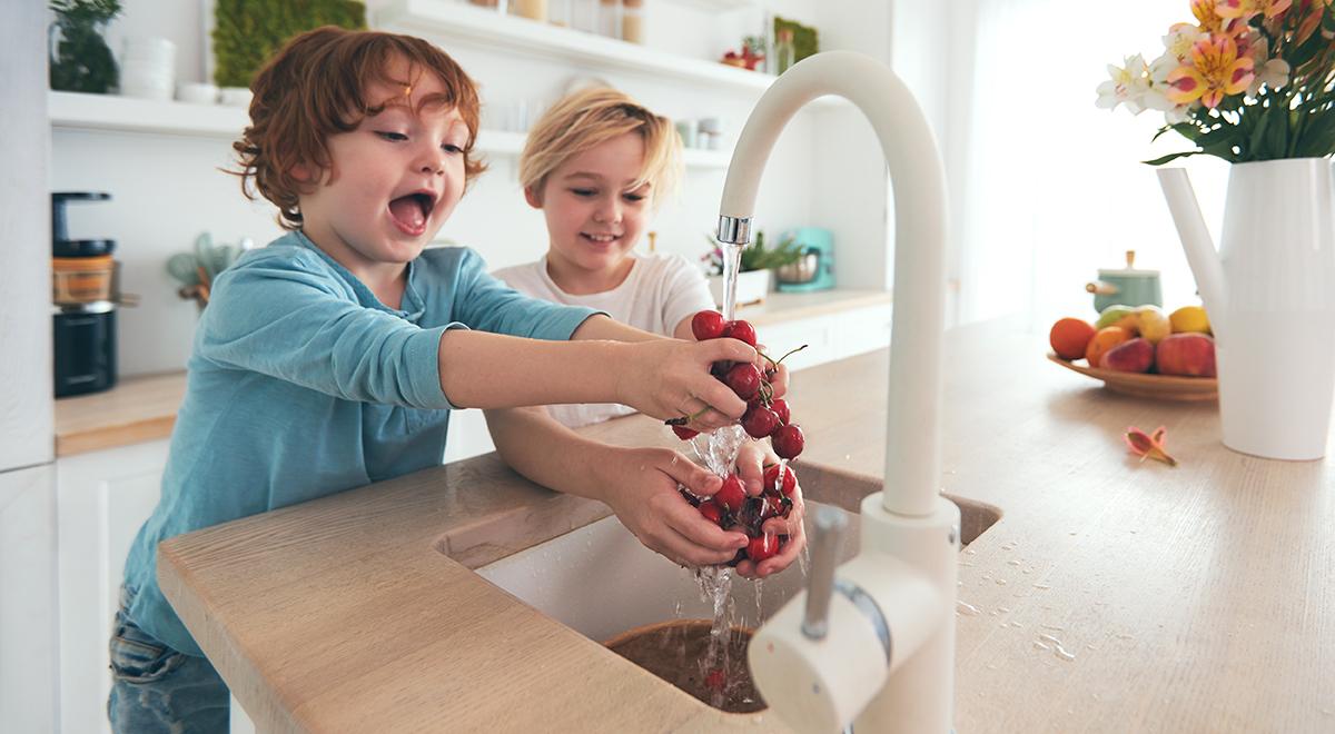 Happy children washing cherries with tap water in kitchen